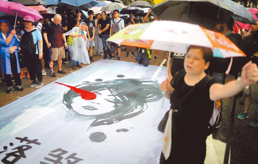 反送中示威者手持雨傘,不畏大雨走向街頭,要求港府回應5大訴求。(路透)