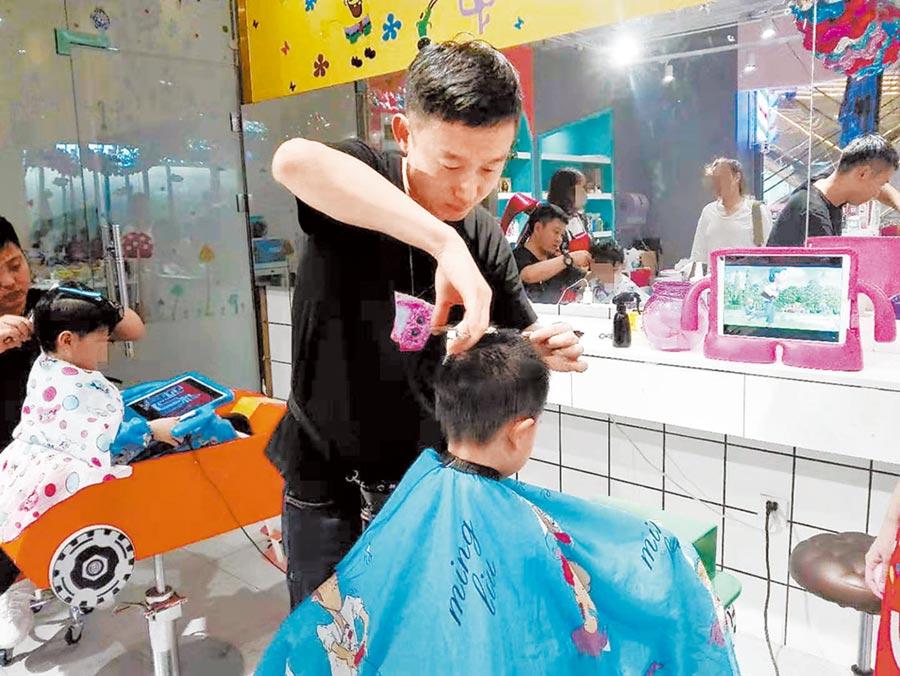 理髮師李偉幫小朋友剪髮。(李倩文攝)