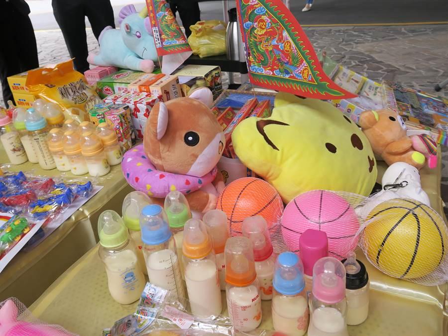 衛生福利部彰化醫院20日舉辦中元普渡法會,有2桌的供品放上裝有鮮奶的奶瓶、糖果餅乾及眾多玩具,供桌還特別低,「方便」嬰靈取用。(吳敏菁翻攝)