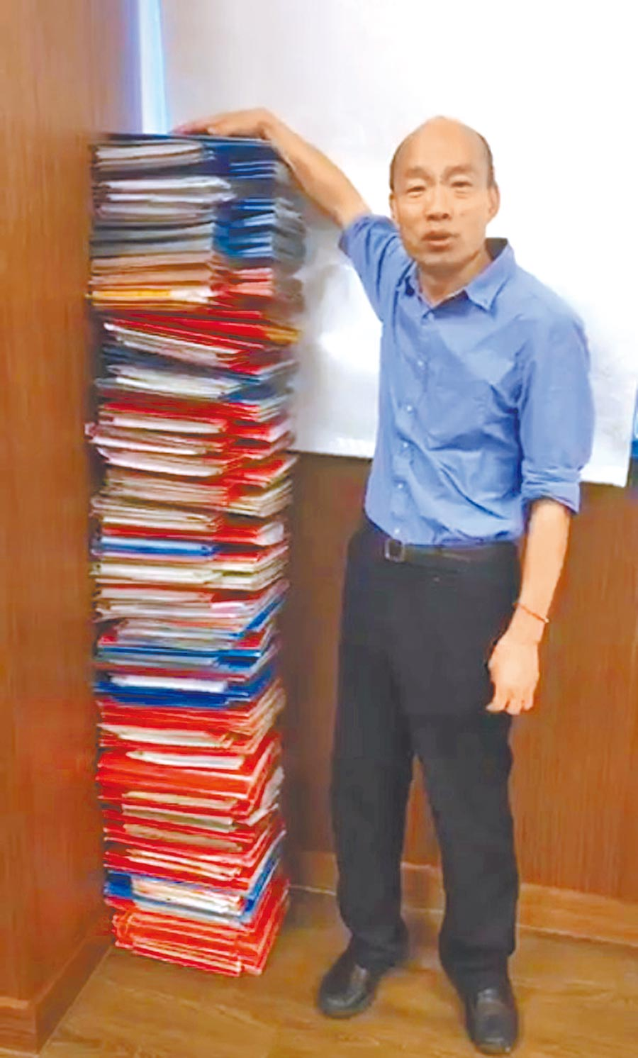 韓國瑜19日中午開直播,堆起和身高一樣高的公文,「和蘇院長PK一下」。(取自韓國瑜臉書)