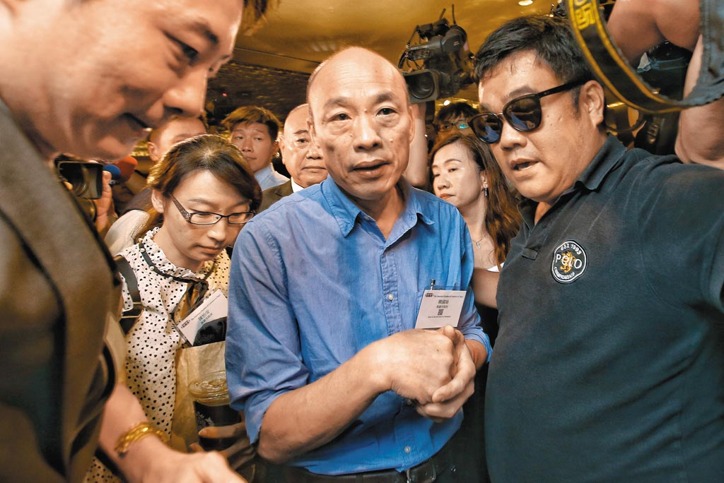 美國商會21日邀請高雄市長韓國瑜(中)發表演講,韓國瑜在媒體包圍下步入會場。在會中韓還自曝38年前曾經幫美國人打過工,大學生活費可說是美商會幫他付的。(杜宜諳攝)