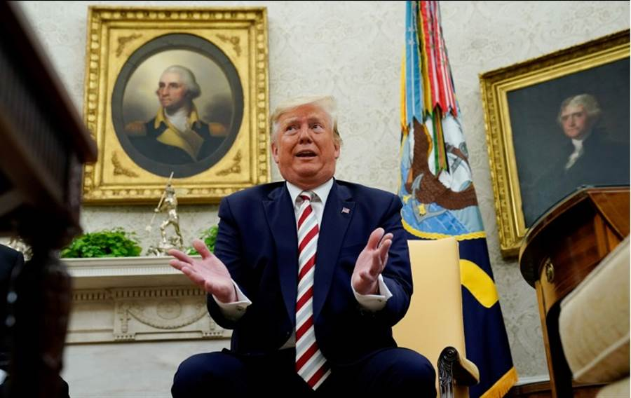 美國總統川普20日在白宮橢圓形辦公室回答記者提問的神情。(路透)