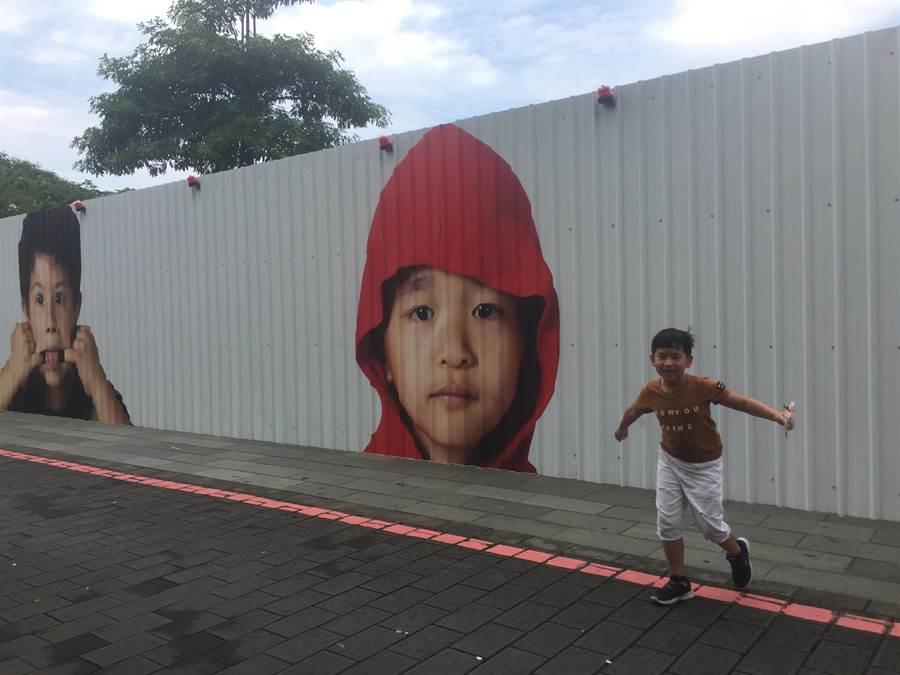 近藤悟集合成功國小100位小朋友的影像,讓工程圍籬變得有故事。(曹婷婷攝)