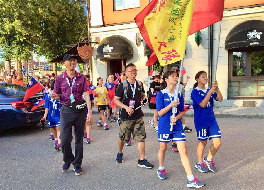 台中市黎明國小女足隊,暑假參加2019瑞典南泰利耶國際分齡賽(Södertälje International Football Cup),由校長徐大偉(左)帶隊,拿著國旗,在瑞典城市裡遊行。(黎明國小提供)