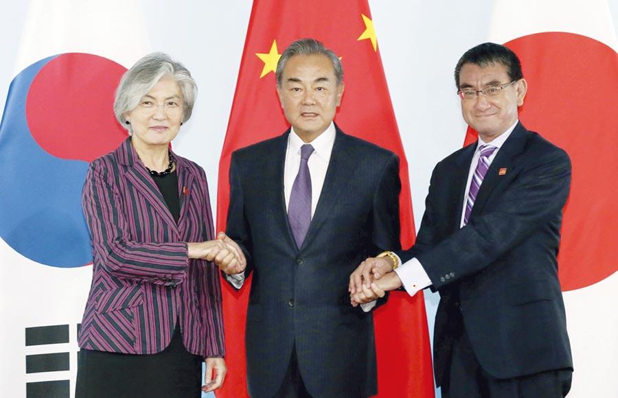 中日韓外長會議在北京舉行,中國國務委員兼外交部長王毅(中)與韓國外長康京和(左)、日本外相河野太郎合影。圖/中新社