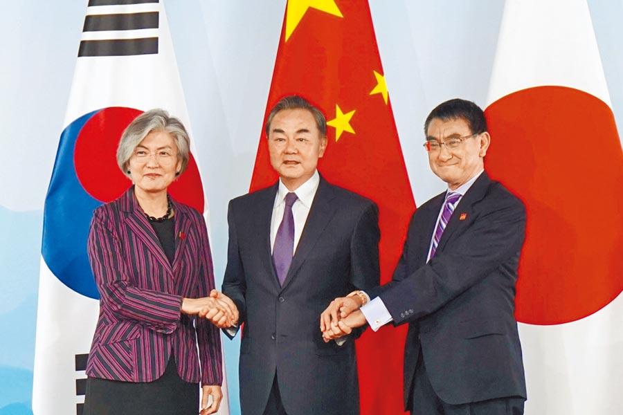 南韩外长康京和(左)、大陆外长王毅(中)与日本外务大臣河野太郎21日在北京会谈,三方一致认为有必加强三国之间的合作。 (美联社)