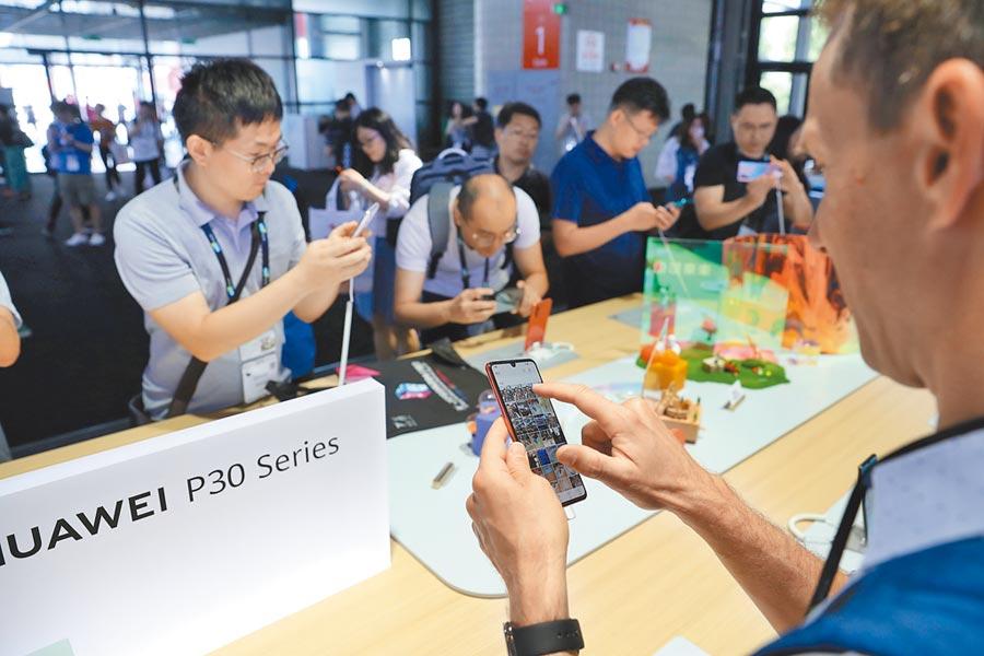 6月11日,2019亚洲消费电子展在上海开幕。受到美国打压的华为展台备受外媒关注。图为境外媒体体验华为手机。(中新社)