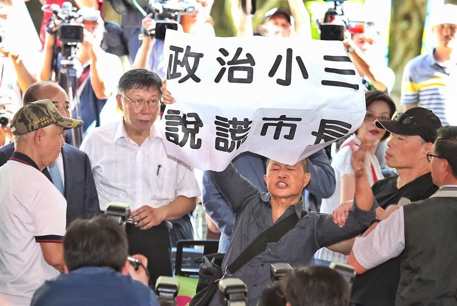 在23日「八二三砲戰紀念音樂饗宴」活動中,民眾在台北市長柯文哲面前高舉海報抗議。(姚志平攝)