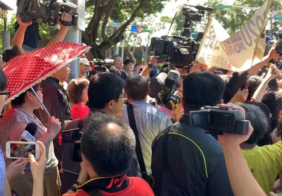 郭柯王今天上午於八二三炮戰紀念公園首度同台,現場有一名撐著紅傘的韓粉不斷高喊「韓國瑜加油」,還要求國民黨開除郭台銘跟王金平黨籍。(林縉明攝)