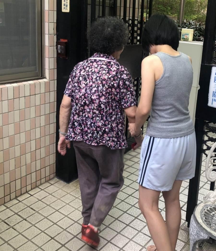 陳姓婦人借住女兒家,外出洗頭後,卻忘了怎麼走回去,員警帶著她挨家挨戶詢問,終於找到她女兒,下樓將她帶回去。(黃國峰翻攝)