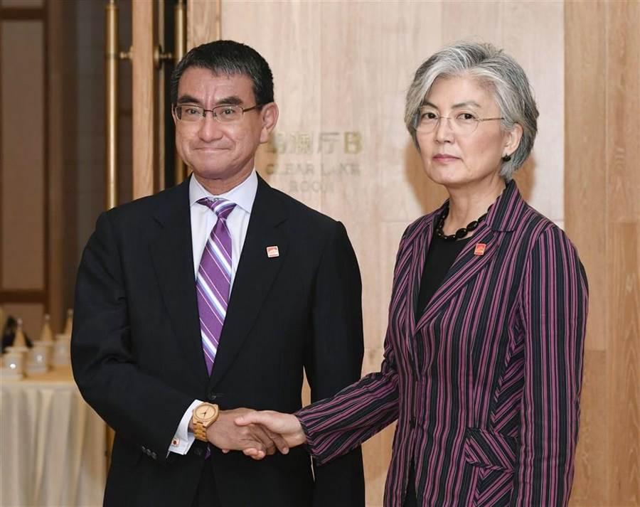 日媒23日報導,日本外務大臣河野太郎(左)21日在北京與南韓外交部長官康京和(右)握手時所戴的「金錶」,被南韓民眾批評是在炫富。河野22日在推特上傳手錶照片並留言寫道「是竹製的,有事嗎」。(中央社/共同社提供)