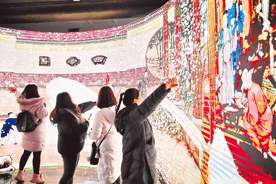 1月23日,民眾在北京故宮博物院舉辦的「宮裡過大年」數字沉浸體驗展上參觀。(新華社)