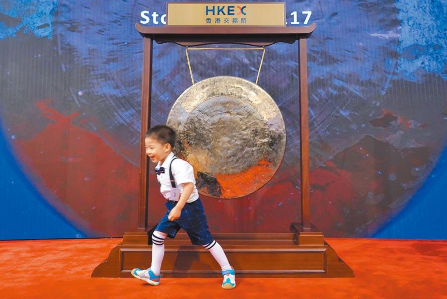 一名小朋友在港交所金融大會堂新股上市儀式結束後從開市銅鑼前跑過。(中新社資料照片)