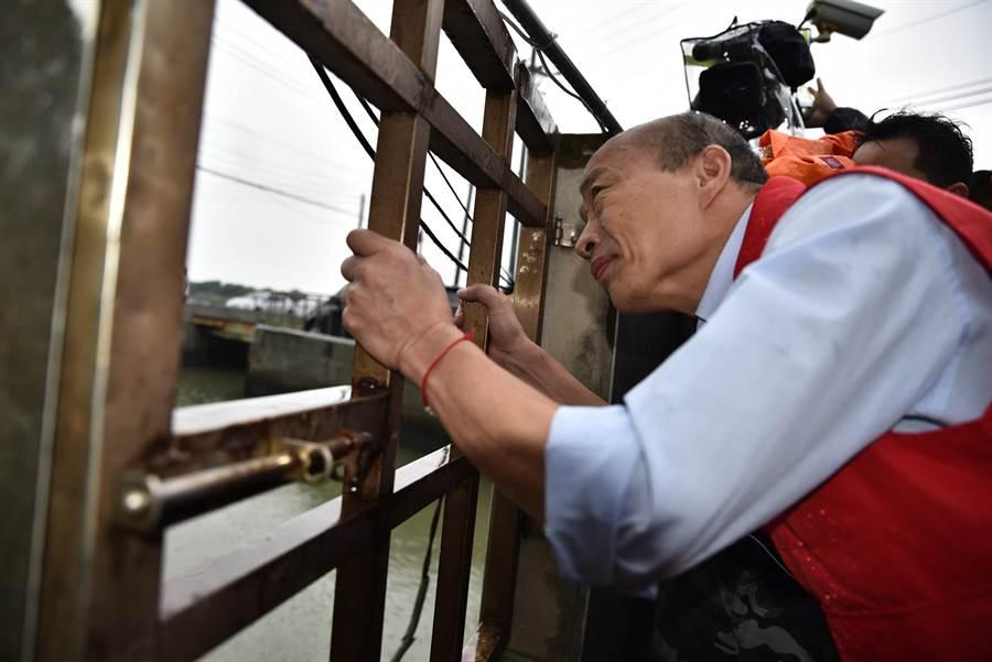 颱風白鹿來襲,高雄市長韓國瑜24日到永安區視察抽水站,他透過柵欄觀看抽水情形。(林瑞益攝)