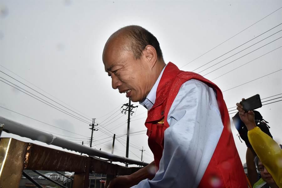 颱風白鹿來襲,高雄市長韓國瑜24日到永安區視察抽水站,他爬上柵欄觀看抽水情形。(林瑞益攝)
