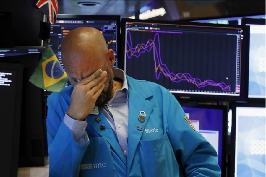 美陸關稅戰又升溫,美股周五被嚇趴。圖為交易員無奈神情。(美聯社)