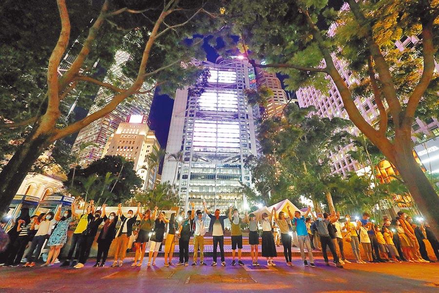 許多香港市民在多個地區響應「香港之路」築人鏈活動,敦促香港實行政治改革。圖為民眾在香港中環手拉手築人鏈的情形。(路透)