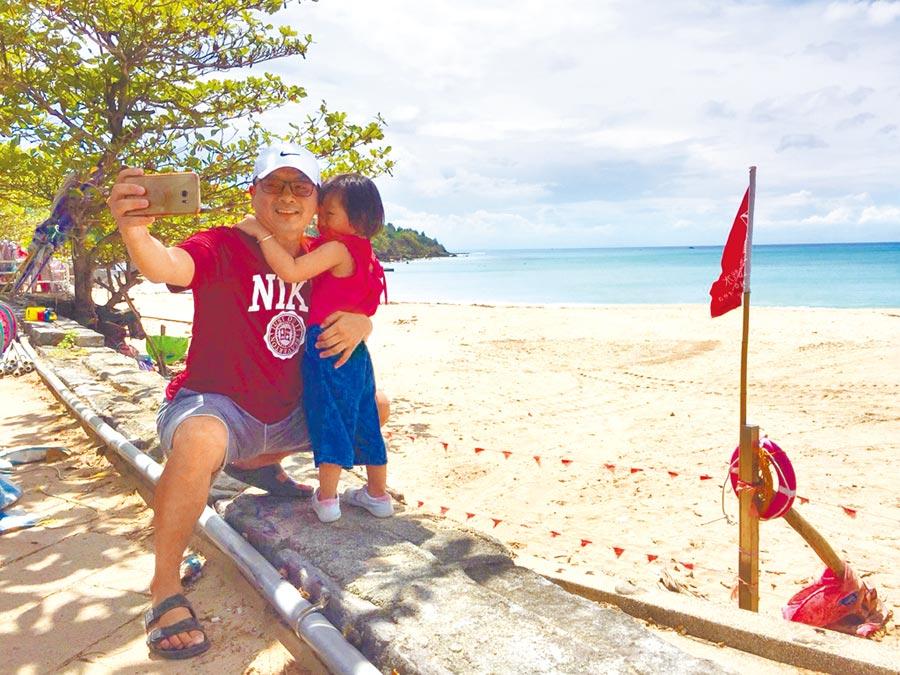 屏東墾丁海邊依規定插紅旗、拉封鎖線,禁止任何人進入,遊客只好站在紅線外望海拍照解悶。(謝佳潾攝)