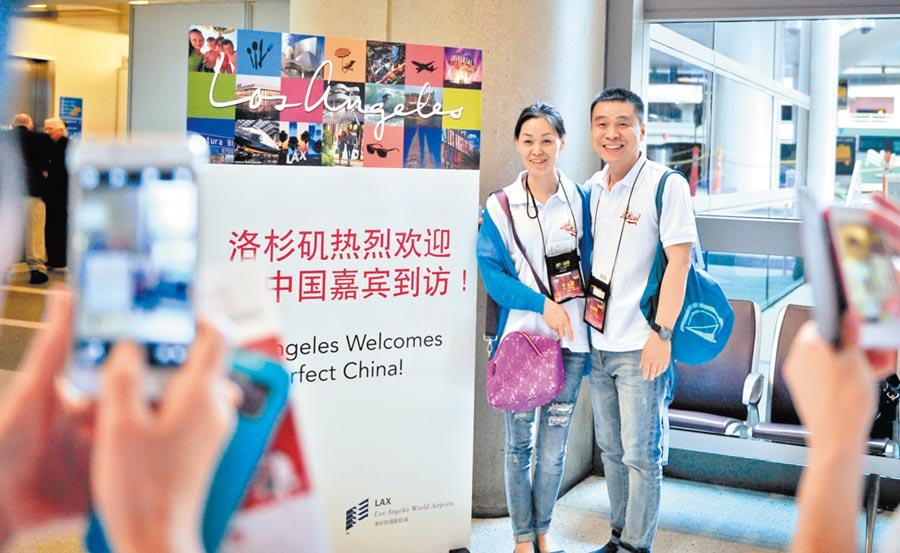 大陸赴美遊客逐漸減少,預計明年將減200萬人次。圖為2014年5月22日,在美國洛杉磯國際機場,兩名陸客與洛杉磯會議及旅遊局的歡迎標語牌合影。(新華社)