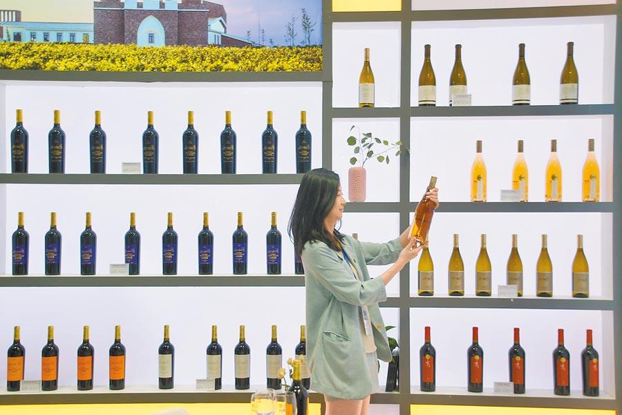 6月28日第十二屆煙台國際葡萄酒博覽會,觀眾在葡萄酒博覽會上觀看展品。(新華社)