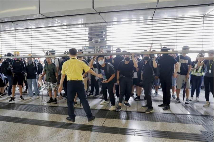 2019年8月24日星期六,車站工作人員試圖阻止示威者進入香港觀塘地鐵站。(美聯社)