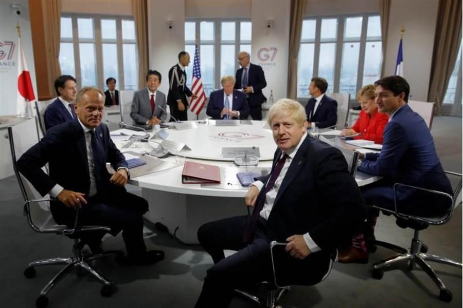 英國新任首相強森(右前)在G7峰會初試啼聲,與各國領袖會談,他身旁為歐洲理事會主席圖斯克。據英媒報導,強森打算告訴歐盟,除非更改協議,否則將把390億脫歐分手費減到剩90億。(路透)
