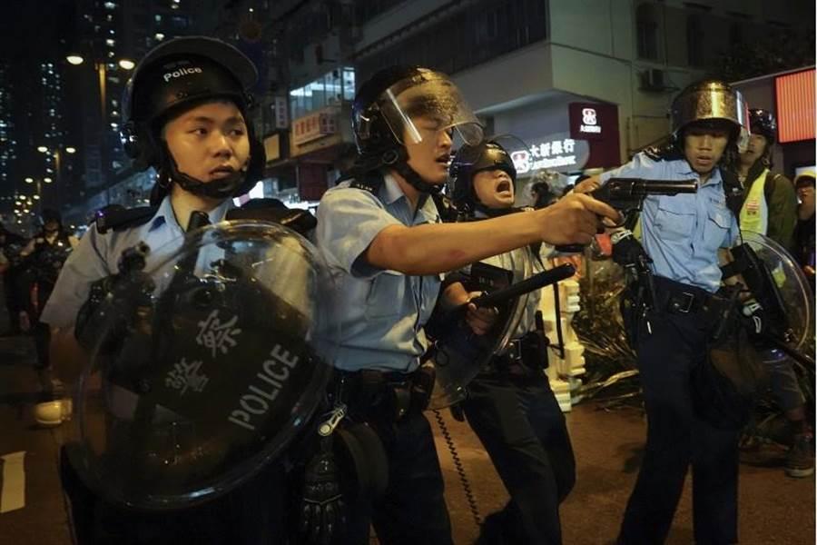 示威者與警察衝突,至少3名警員拔出左輪手槍對向示威者,傳出槍響。(美聯社)