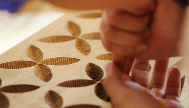 玉東國中木工班學生製作的傢俱上面,結合傳統文化的葉子圖騰佔有相當的比重,耐心不夠的女學生常常刻葉子刻到哭。(季志翔攝)