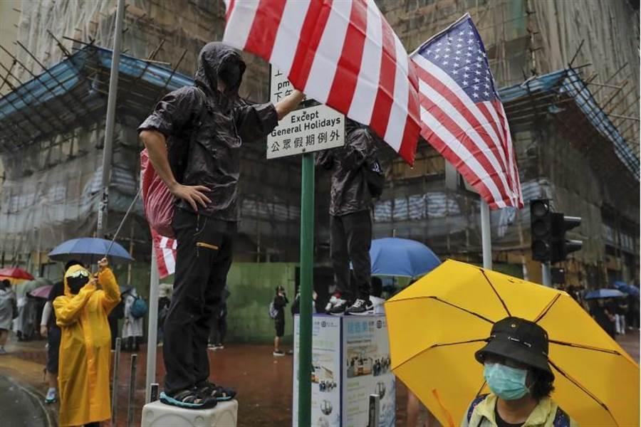 8月25日香港抗爭活動再升級,圖為示威者向警方揮舞美國國旗。(美聯社)