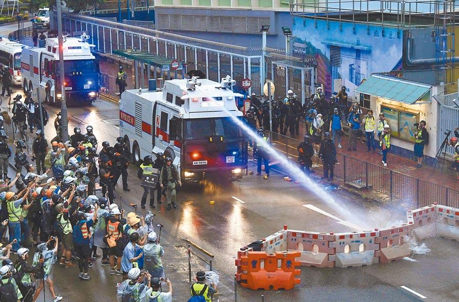8月25日,水炮車協助香港警員清除示威人士築起的路障。(中新社)