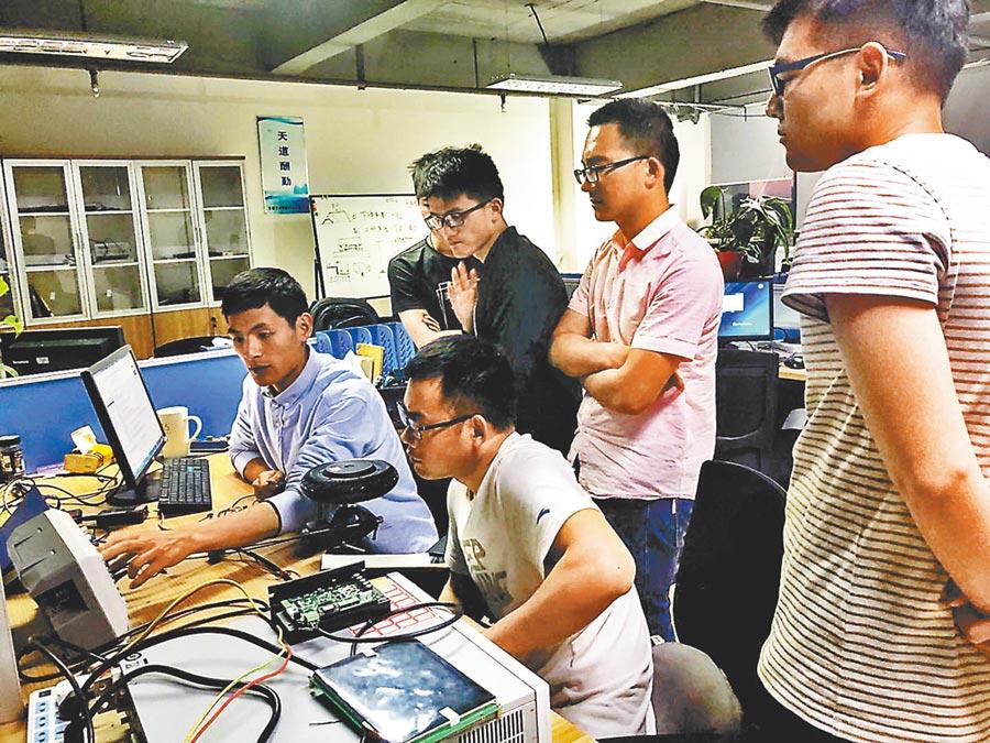 甄聖超(左一)和科研團隊在實驗室就研發進行討論。