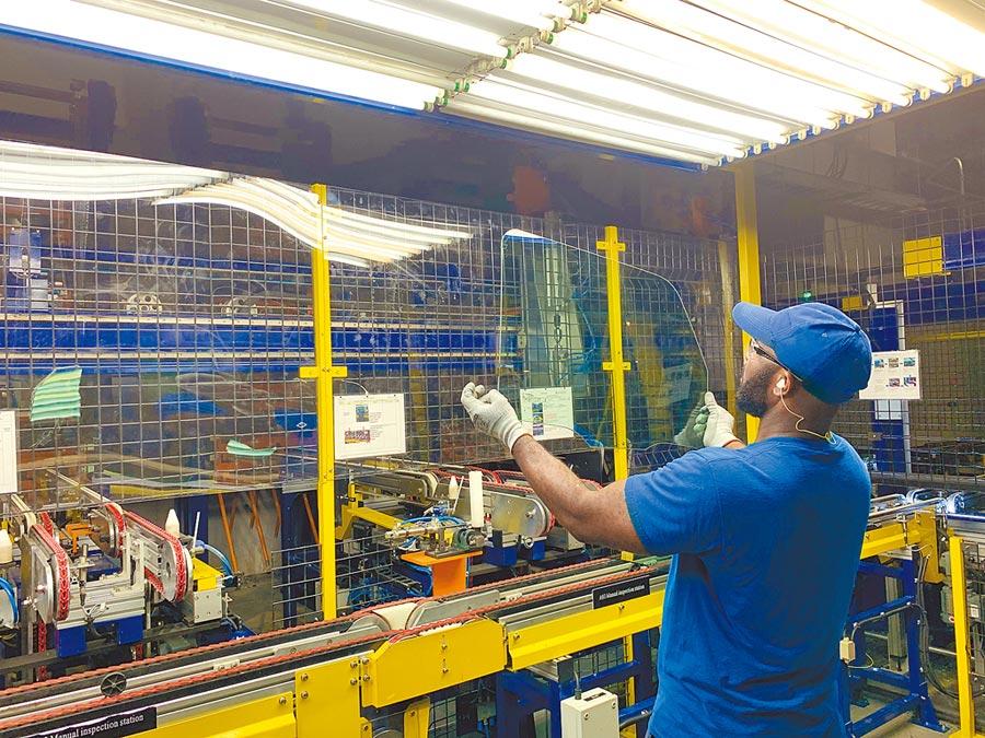8月7日,大陸福耀集團收購美國通用汽車一家廢棄廠,重生玻璃工廠。圖為一名美國員工檢驗玻璃外觀。(新華社)