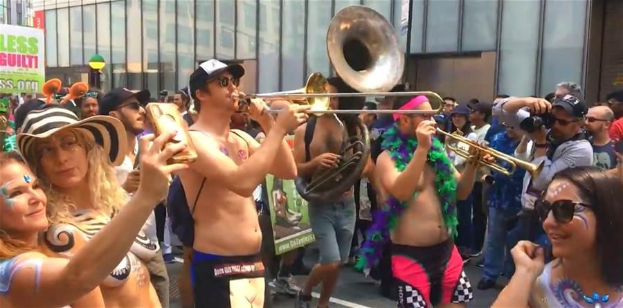 百位男女在紐約曼哈頓街頭展開行動訴求,認為在公共場域赤膊是一件自然的、無須感到羞恥的事。(圖/Youtube)