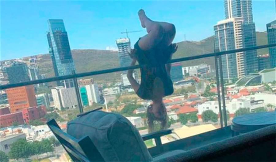 洛佩斯挑戰在8樓陽台倒掛金鉤,圖片可見她的雙手已經離開欄杆。(圖/翻攝自IG)