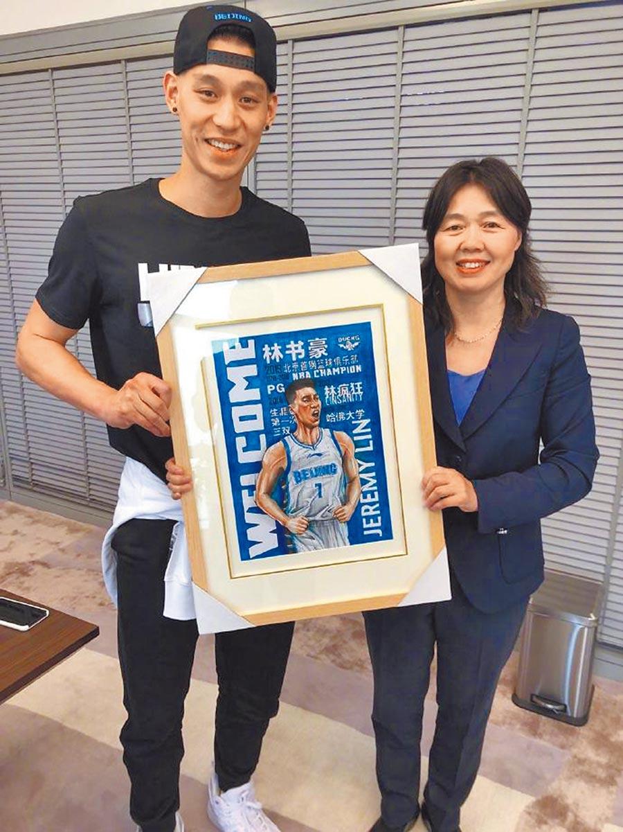 首鋼體育總裁秦曉雯(右)贈送加盟海報給林書豪(左)。(翻攝北京首鋼微博)