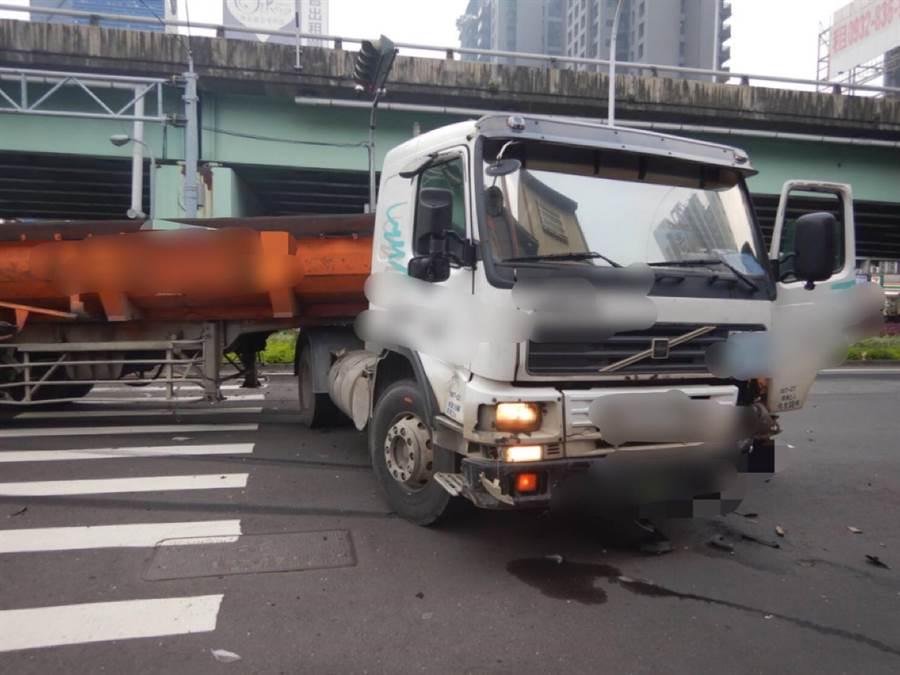 砂石車被汽車強力衝撞後,龐大的車頭與車身成為V型,停在台灣大道上。(盧金足翻攝)
