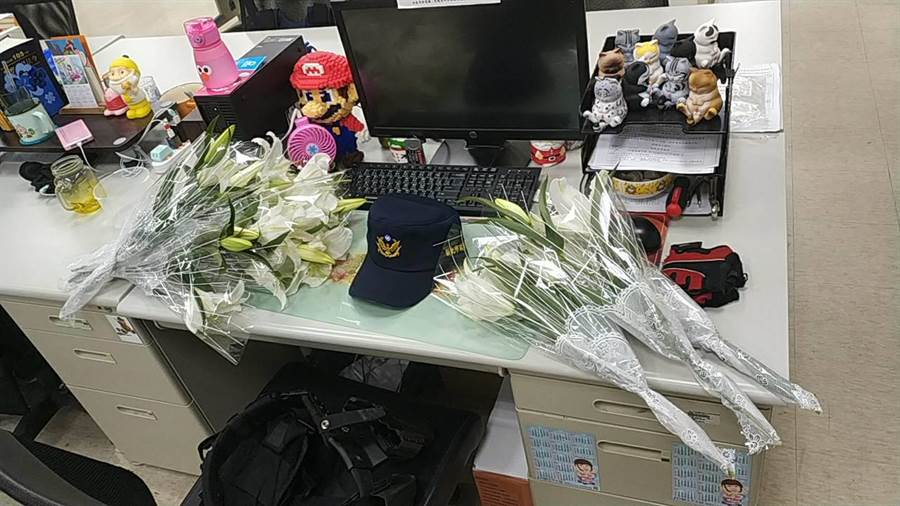 薛員的辦公桌上已放滿同仁悼念他的鮮花。(王揚傑翻攝)