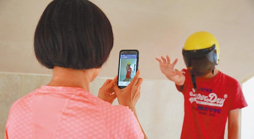 只要碰觸一鍵,便可同時開啟發送警報訊息到校園值勤室、傳送現場影像照片、火速與校安人員對話等功能。(中山大學提供)