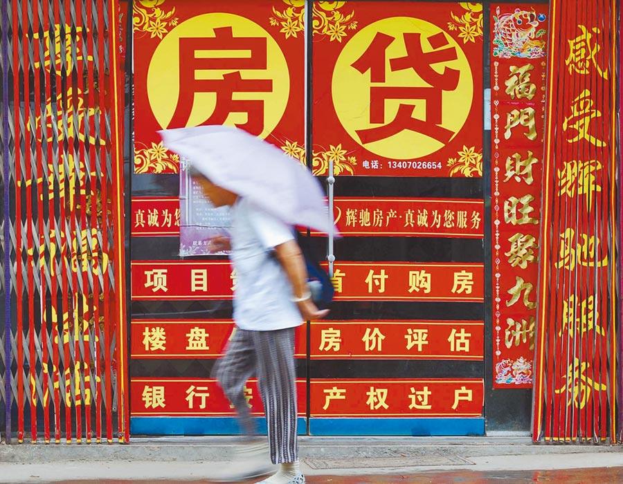 大陸這波「降息」風可能不會使房貸利率下降。圖為行人從江西省一家房產仲介所前經過。(新華社資料照片)