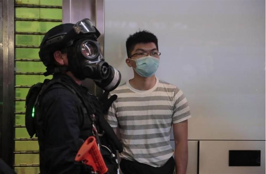 一名貌似黃之鋒男子蒙面被港警逮捕。(美聯社)