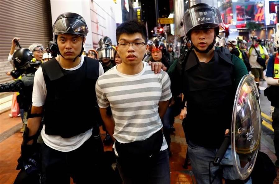 一名貌似黃之鋒男子蒙面被港警逮捕,摘下面罩後發現不是黃之鋒。(路透)