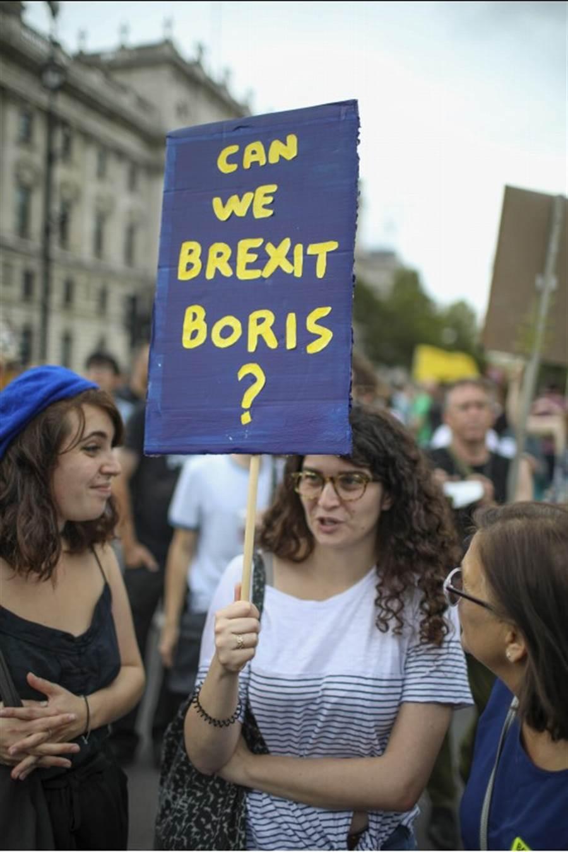 英國首相強森出招迫使國會提早休會,朝野譁然,英國各地昨天出現反對國會休會示威,抗議民眾舉著上寫「我們可以『脫強森』嗎?」的標語牌。(美聯社)