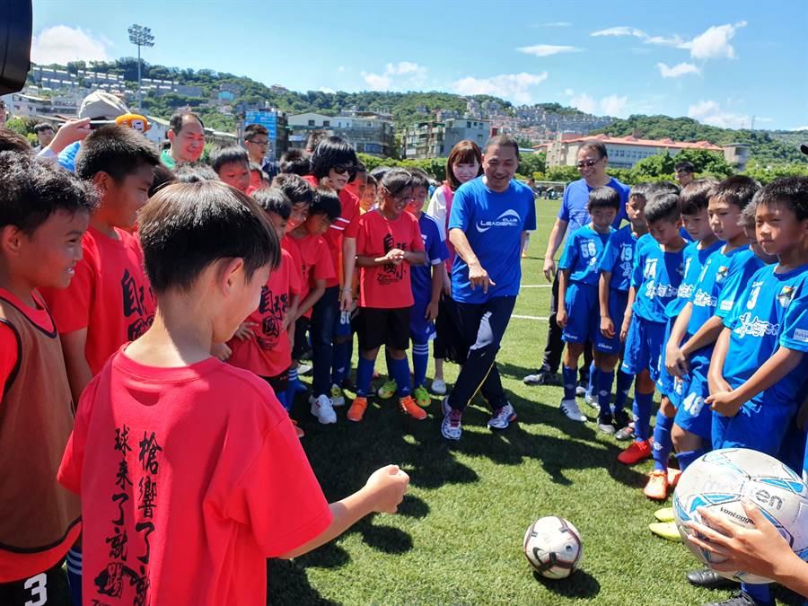 新北市長侯友宜1日上午前往錦和運動公園與國小足球隊一起踢足球。(葉書宏攝)