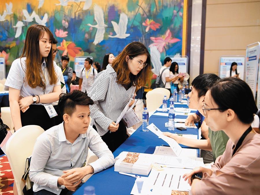 6月15日,第十四屆台灣專業人才就業創業暨台生實習見習廈門對接會在廈門市舉行,幾名台灣青年在對接會上與招聘人員交流。(新華社)