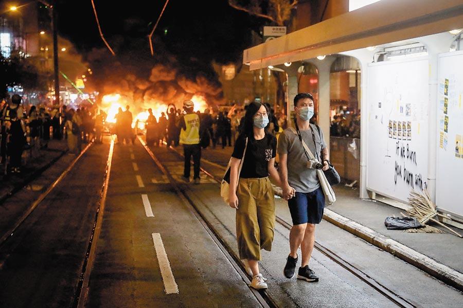 8月31日傍晚,香港暴力抗爭,灣仔一帶街道更燃起熊熊火光。也有一般民眾淡然以對,默默走離現場。(中央社)