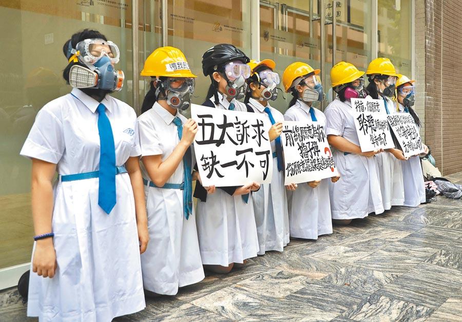 林鄭月娥母校嘉諾撒聖方濟各書院外,8名學妹響應罷課,戴頭盔面罩,跪地舉著「五大訴求,缺一不可」等標語。(美聯社)