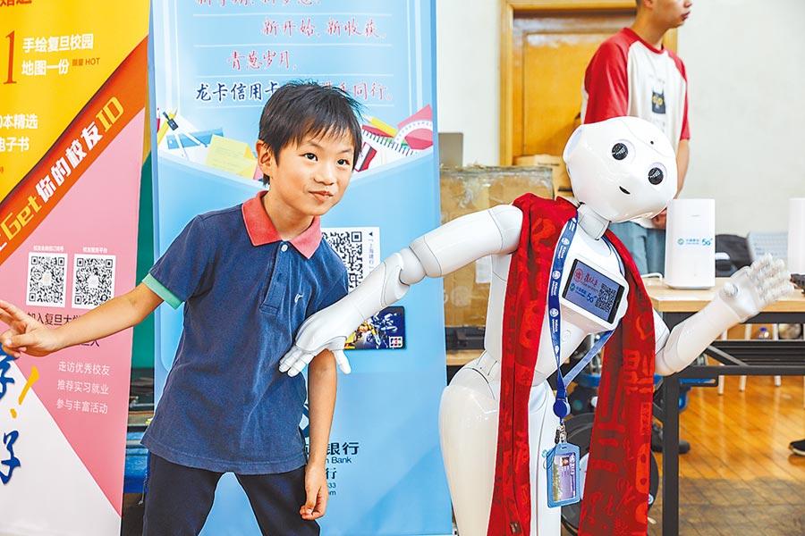 小朋友在復旦大學開心與機器人「曉應」合影。(取自微博@復旦大學)