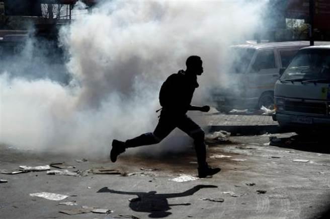 南非暴亂,一名南子在約翰尼斯堡東郊打劫一家商店後,於警方發射催淚瓦斯時逃離現場。(美聯社)