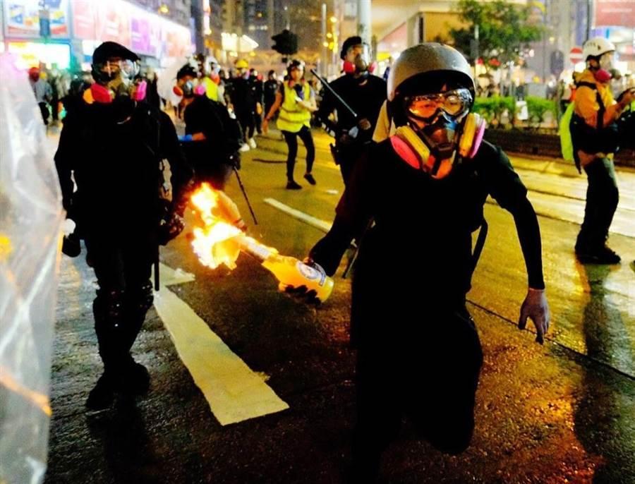 香港示威者向警察丟擲汽油彈。(新華社)