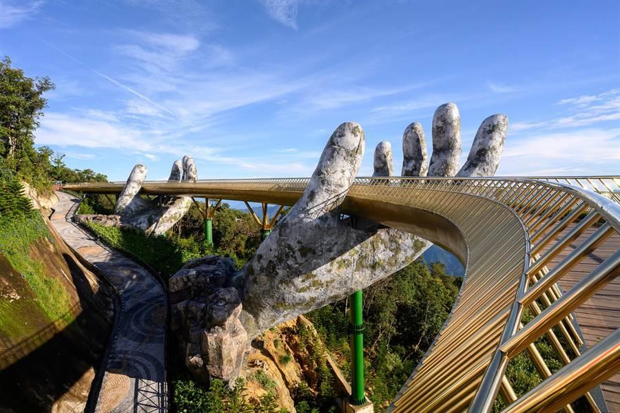 越南峴港度假勝地巴拿馬山上的「黃金橋」為2018年開放的新景點,巨手捧橋的設計吸引眾人目光。(長榮航空提供/陳祐誠傳真)